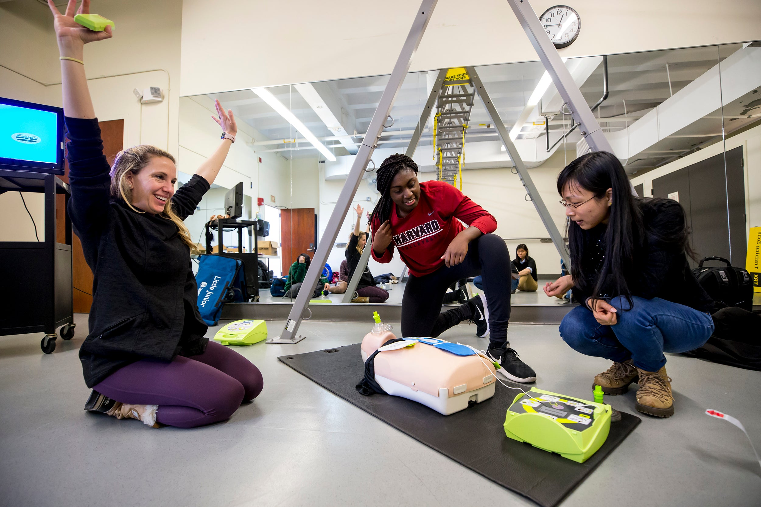 Fitness instructor Christina Hoff (from left), Sope Adeleye '20, and visiting scholar Qingqing He '18 participate in American Heart Association Heart Saver CPR and AED (automated external defibrillator) training for adults, children, and infants. Rose Lincoln/Harvard Staff Photographer