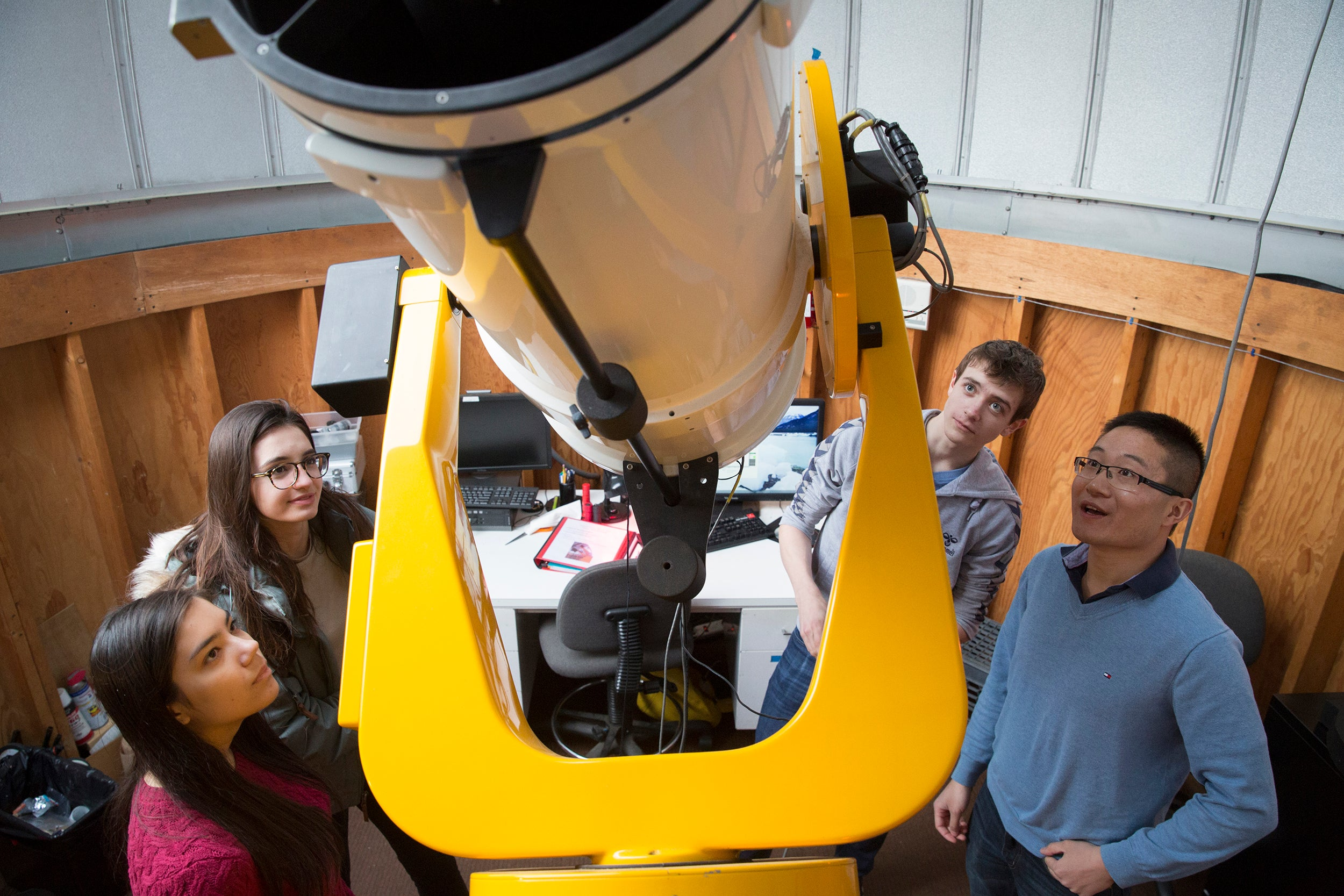 CRLS students Sophia Sonnert (from left), Tatiana Athanasopoulos, and Jonas Hansen meet with Harvard postdoc George Zhou at the Clay Telescope at the Science Center. Zhou is a mentor in the Science Research Mentoring Program at the CfA.