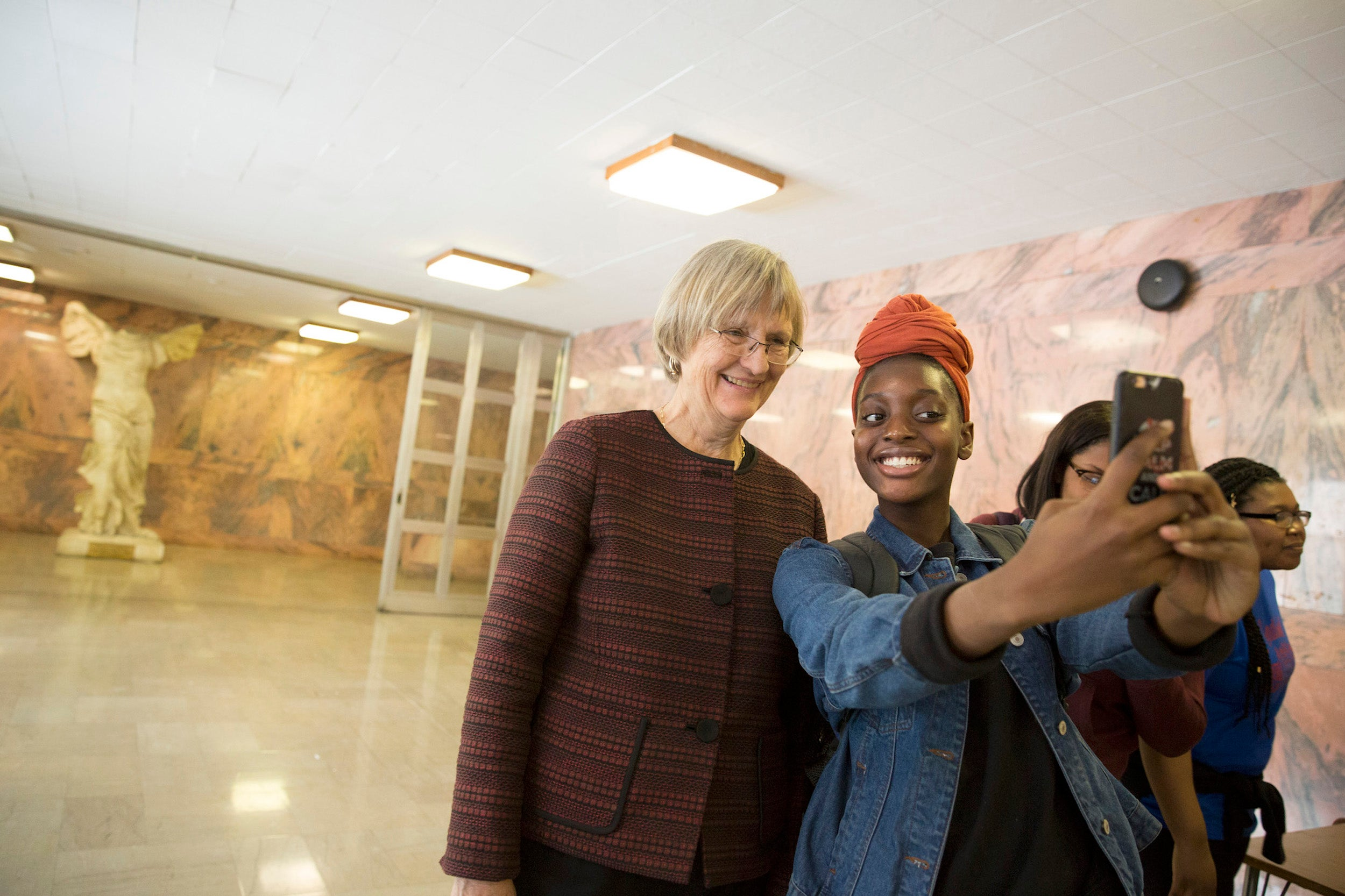 """""""It feels good to know that somebody of her stature wants to come to speak to us,"""" said Amanda Smith, pictured taking a selfie with Harvard President Drew Faust."""