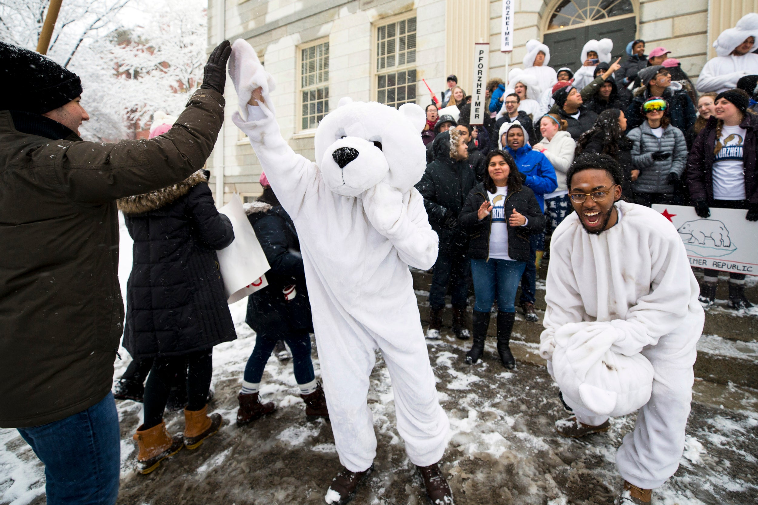 Julius Wade (right) and fellow PfoHo residents celebrate being the second to arrive at the John Harvard statue for the annual delivery of housing assignments.