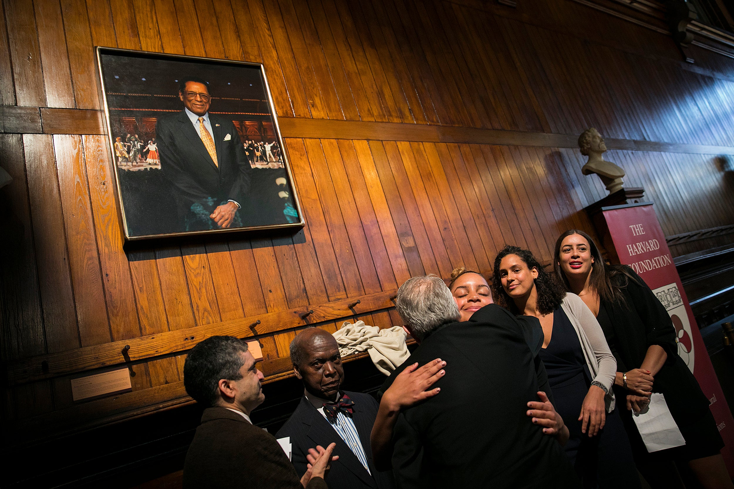 Rakesh Khurana (from left), David L. Evans, Portraiture Project Artist Stephen Coit '71, and daughters of S. Allen Counter Maya, Olivia, and Philippa embrace under the newly unveiled portrait of the late founder of the Harvard Foundation for Intercultural and Race Relations.