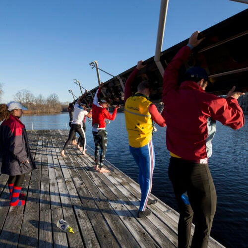 "Jennie Kunes calls out instructions to her ""eights"" as they set their boat in the water. ""One rower putting in more effort doesn't make a measureable difference unless the entire crew does it with them, and the coxswain has to be attuned to the crew's mentality and technique to keep everyone together."""