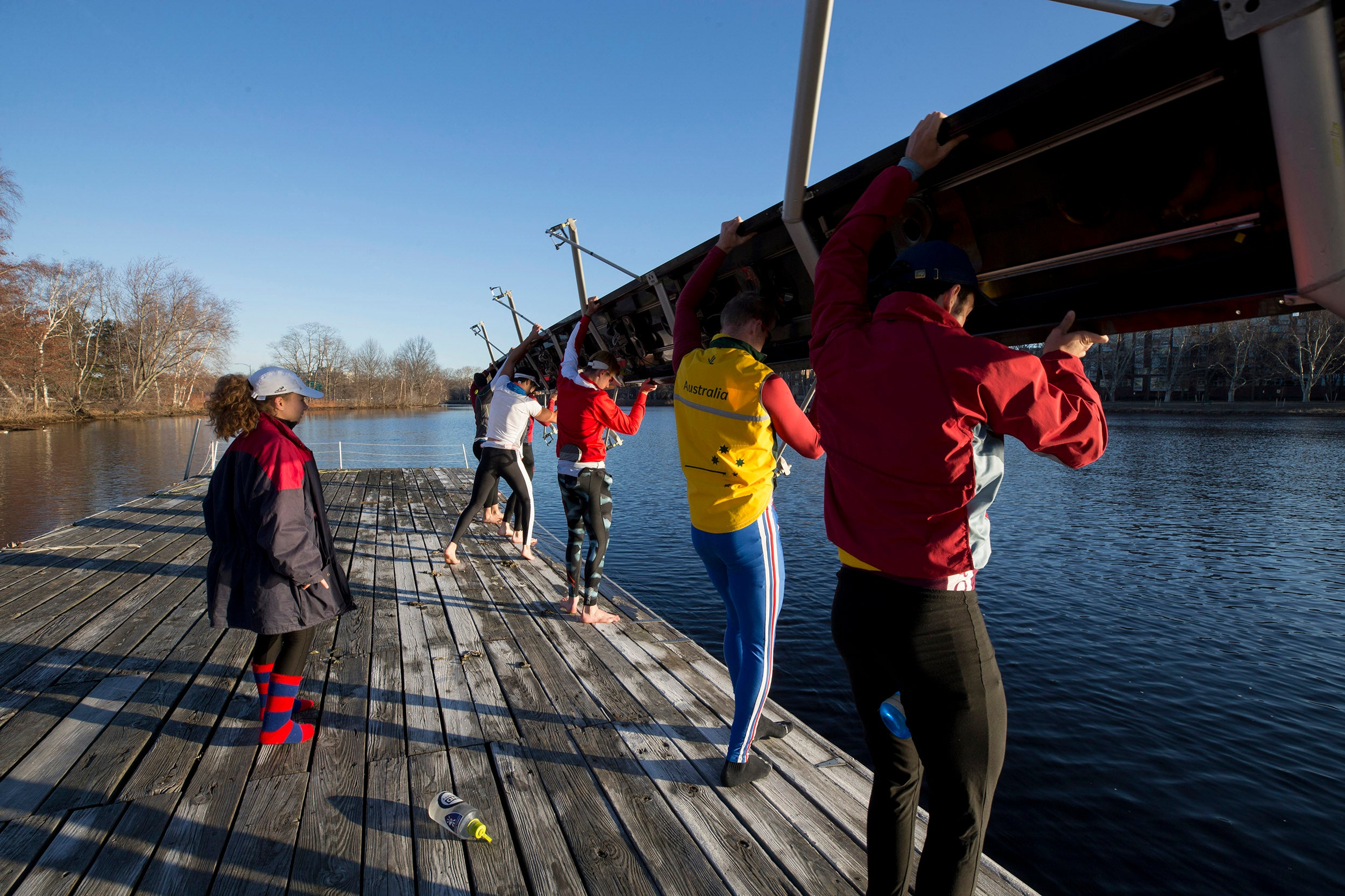 """Jennie Kunes calls out instructions to her """"eights"""" as they set their boat in the water. """"One rower putting in more effort doesn't make a measureable difference unless the entire crew does it with them, and the coxswain has to be attuned to the crew's mentality and technique to keep everyone together."""""""