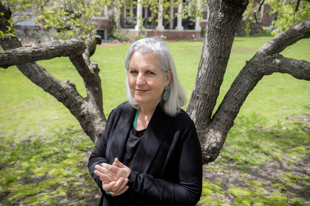 Terry Tempest Williams stands with hands clasped in front of a tree.
