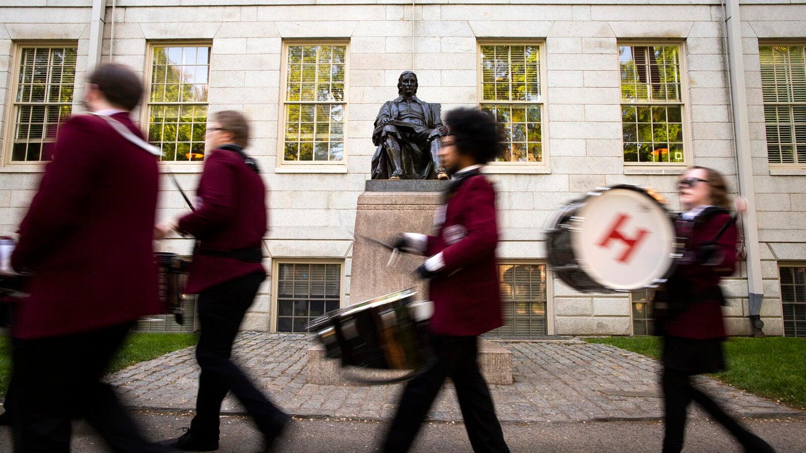 Graduates walk past John Harvard Statue.