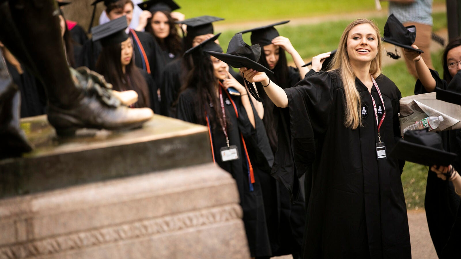 Graduates file past the John Harvard Statue.
