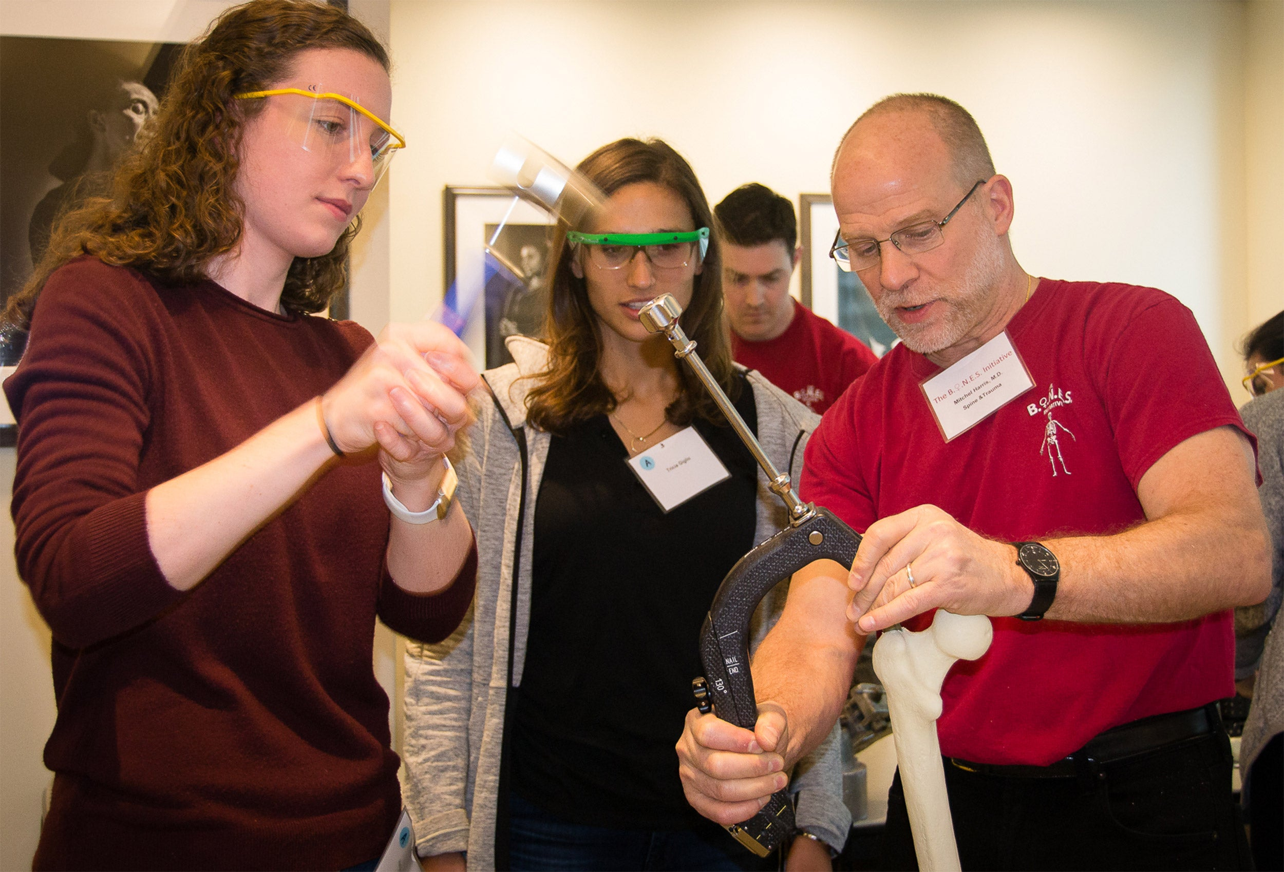 Mitchel Harris demonstrates to Heleyn Grissom (left) and Tricia Giglio methods to place an intramedullary nail on a femur sawbones model.