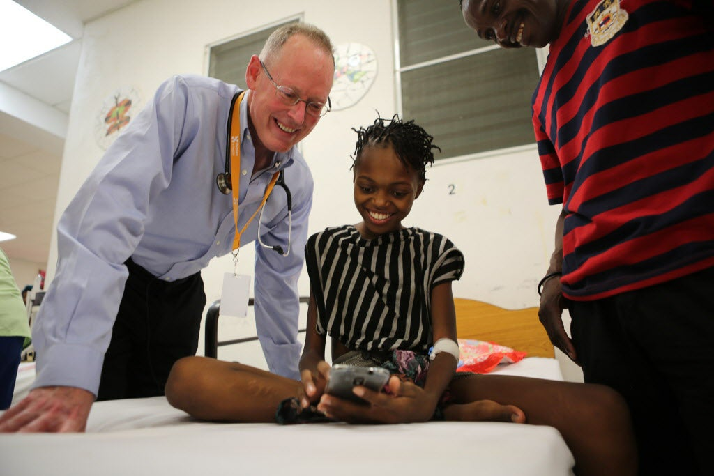 Dr. Paul Farmer speaks with 12-year-old being treated for jaundice at University Hospital in Haiti.