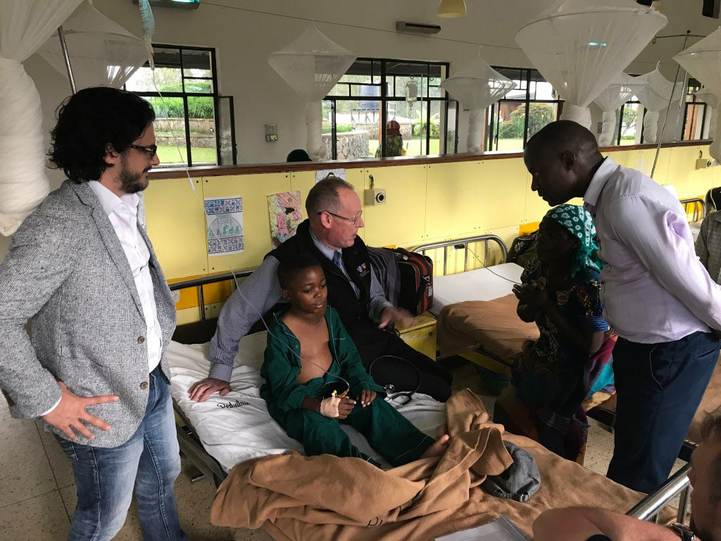 Paul Farmer and other doctors visit a 10-year-old Hodgkin Lymphoma patient in a hospital in Rwanda.