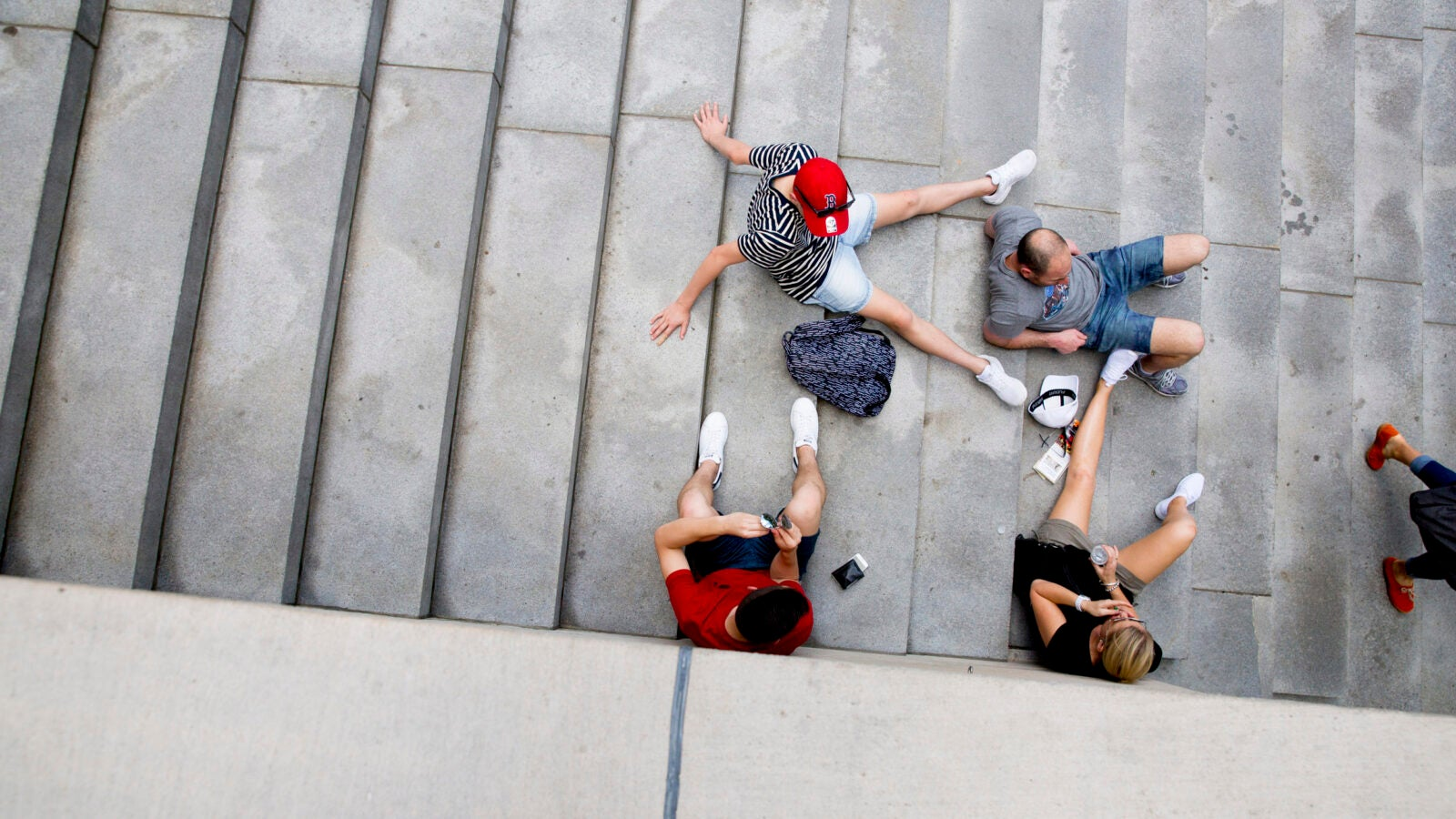 A red cap, T-shirt, and pair of shoes brighten the steps of Widener Library.