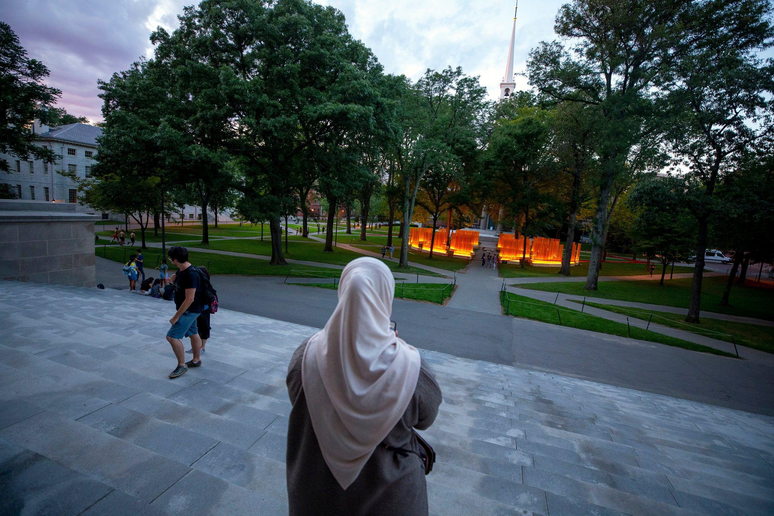 """From the steps of Widener Library, a woman photographs """"Autumn (... Nothing Personal),"""" a public sculpture by artist Teresita Fernández recently installed in Harvard Yard at Tercentenary Theatre."""