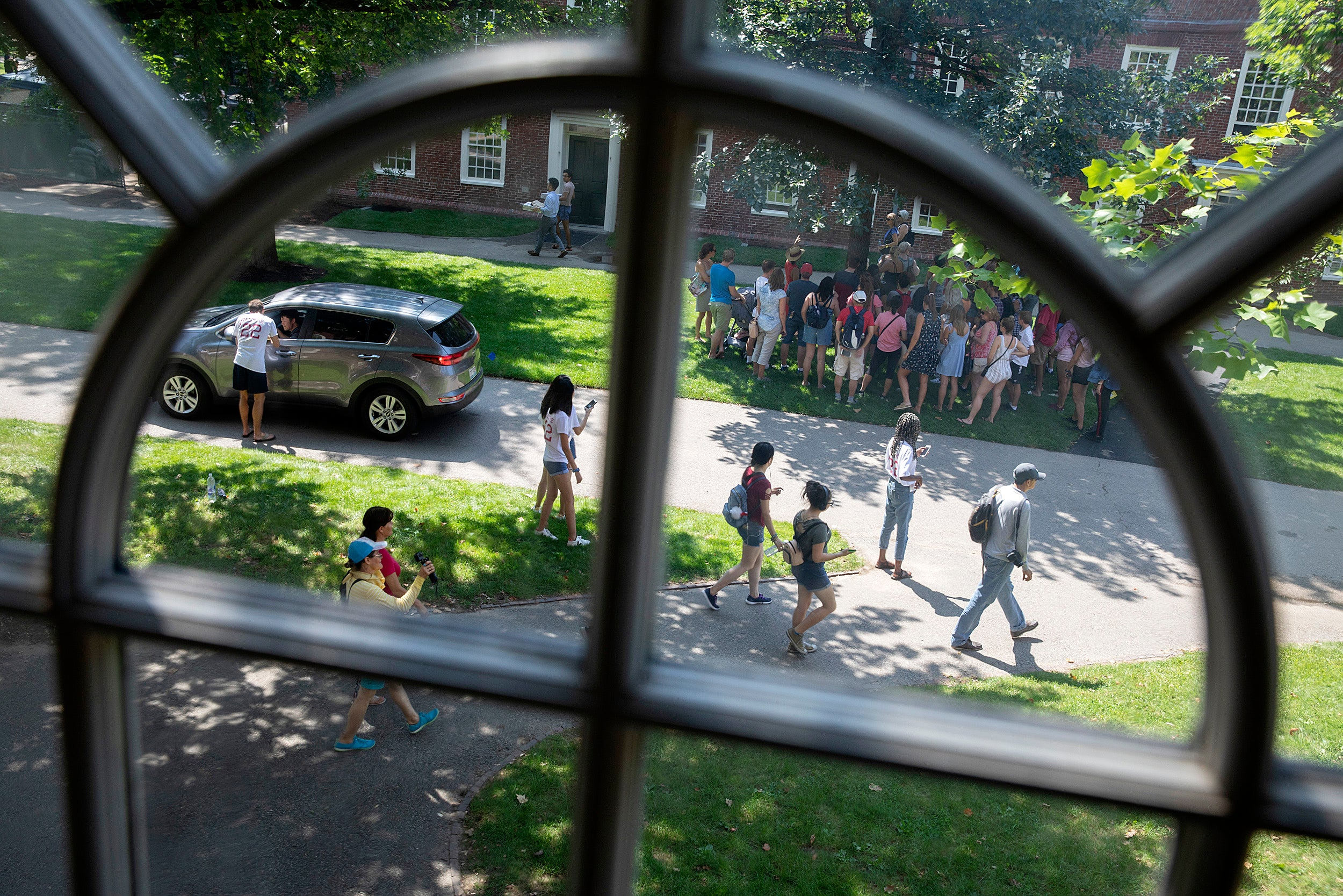 Students and their families mingle outside Mass Hall during move-in day. They are framed by a Harvard Hall window.