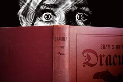 "Illustration of frightened reader peering over ""Dracula."""