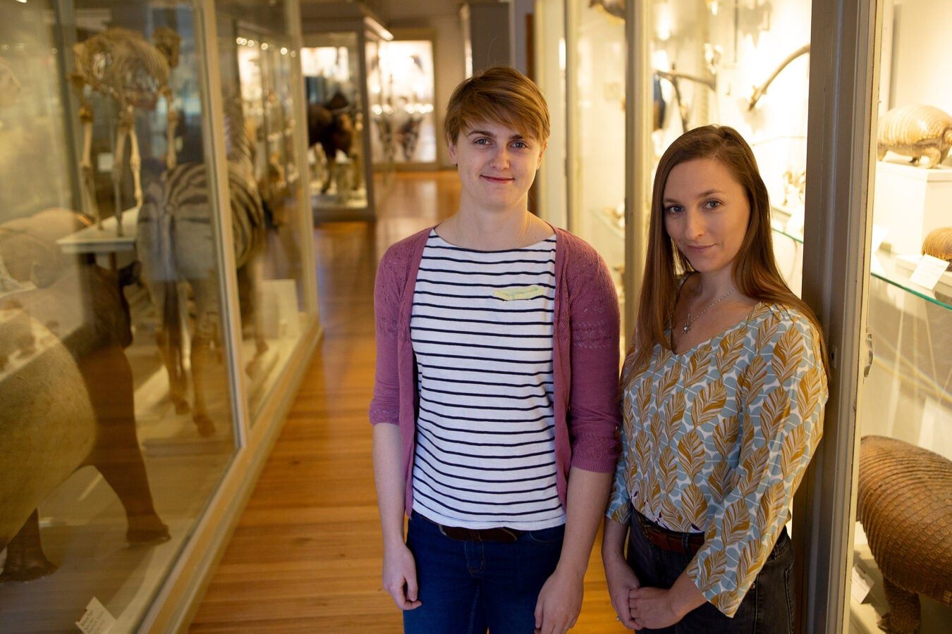 Sophie Regnault and Stephanie Pierce stand in front of Harvard Natural History Museum exhibits.