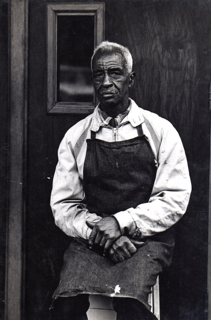 Man wearing apron seated on Blake Avenue in New York, 1965.