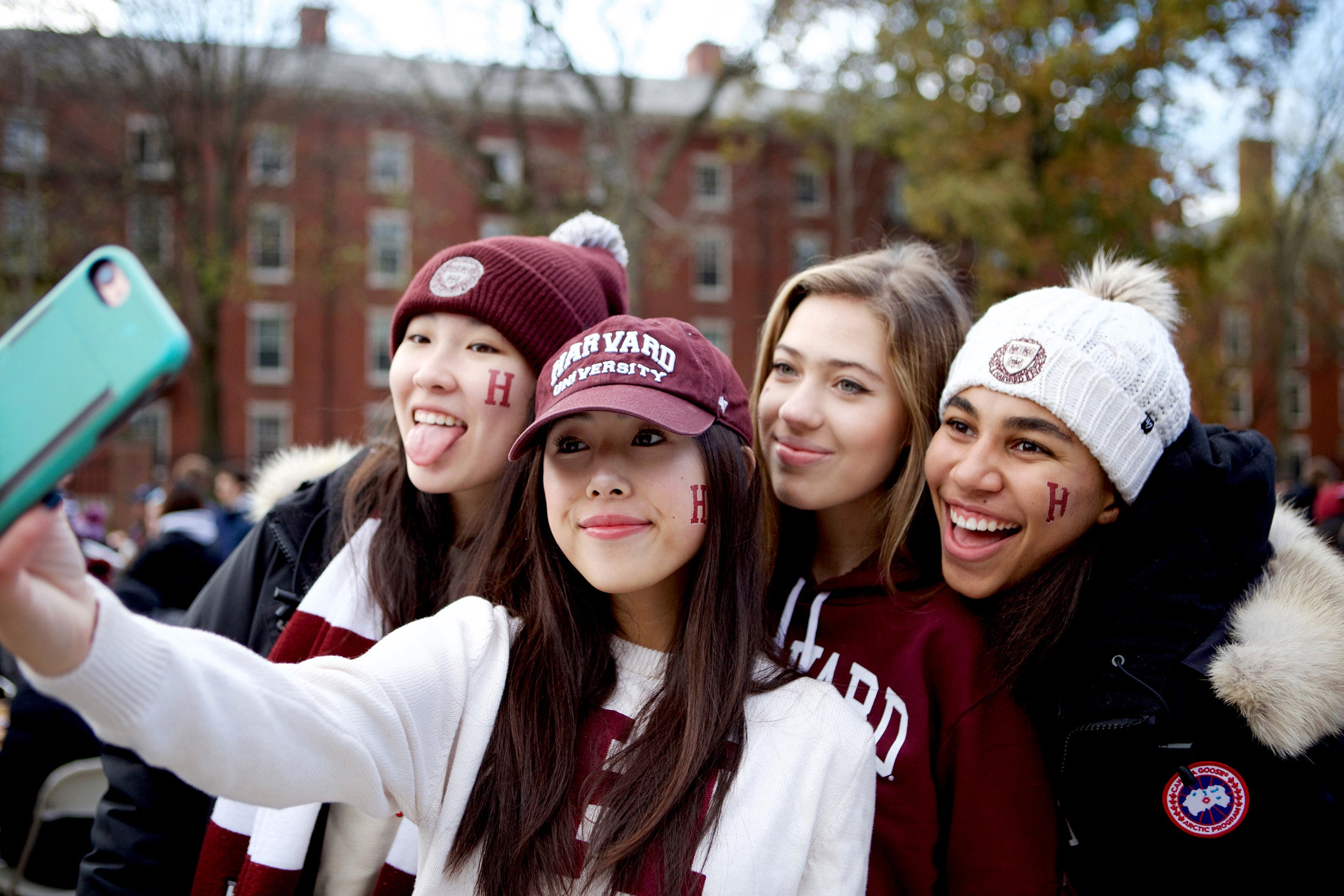 Harvard students Lucy Lu (from left), Elyse Pham, Isabel Isselbacher, and Alexandra Diggs pose for a selfie at a tailgate party in Science Center Plaza before they headed to the Harvard-Yale game at Fenway Park. Photo by Olivia Falcigno
