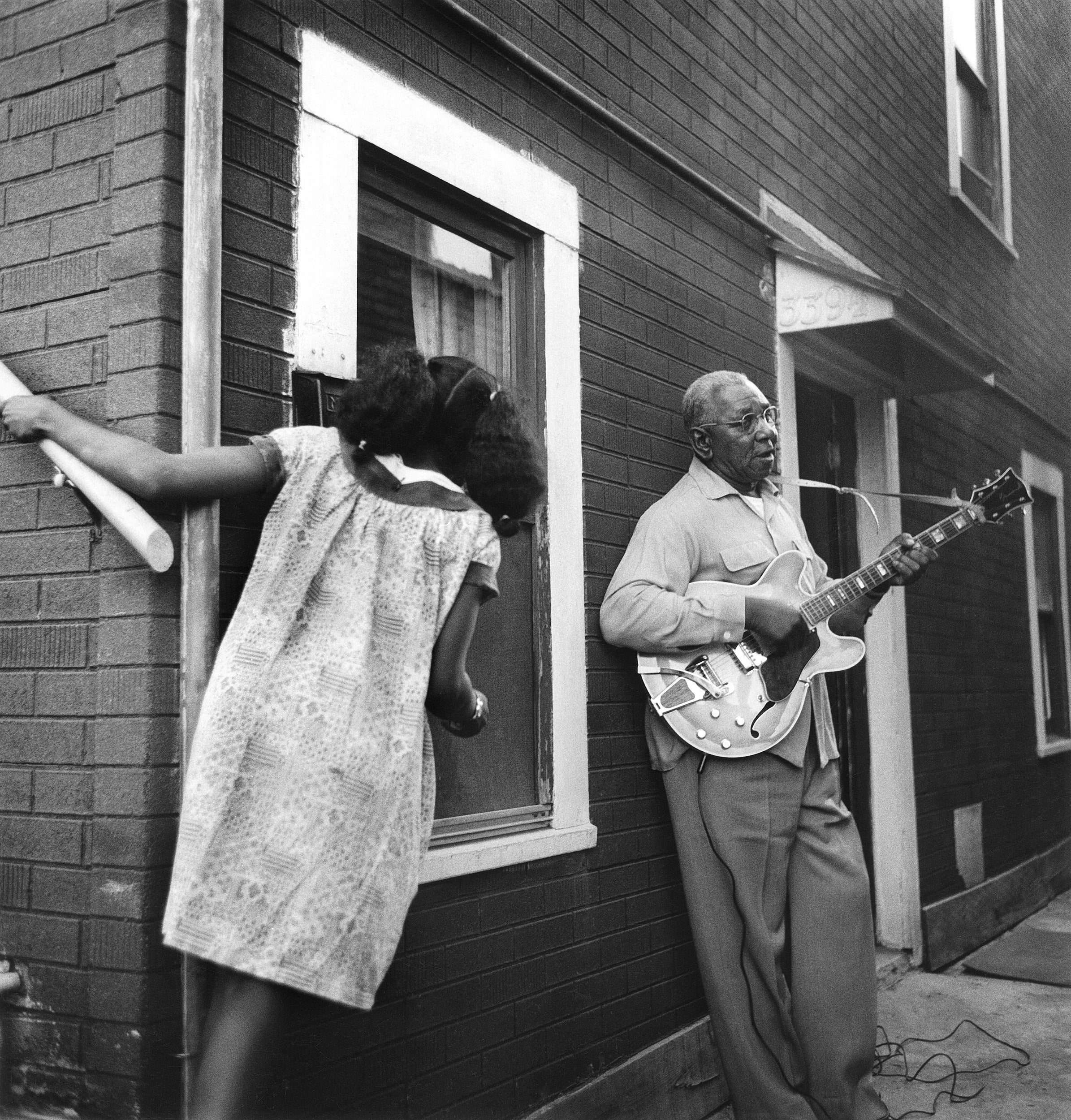 Girl watches man play guitar in 1965.