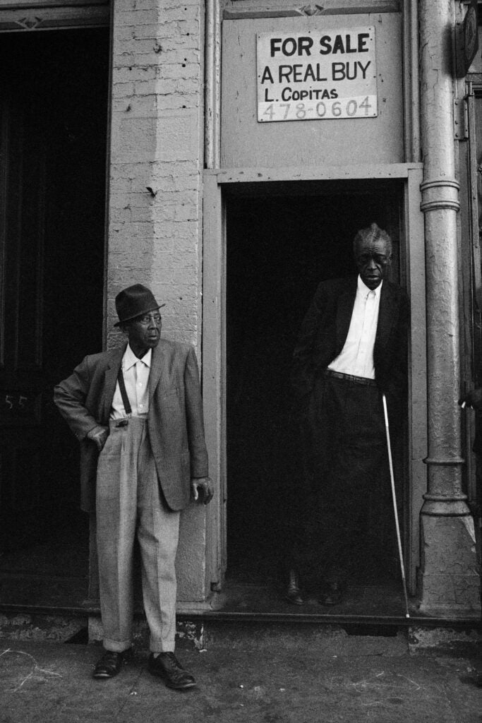 Two men stand in front of building with For Sale sign in Chicago in 1966.