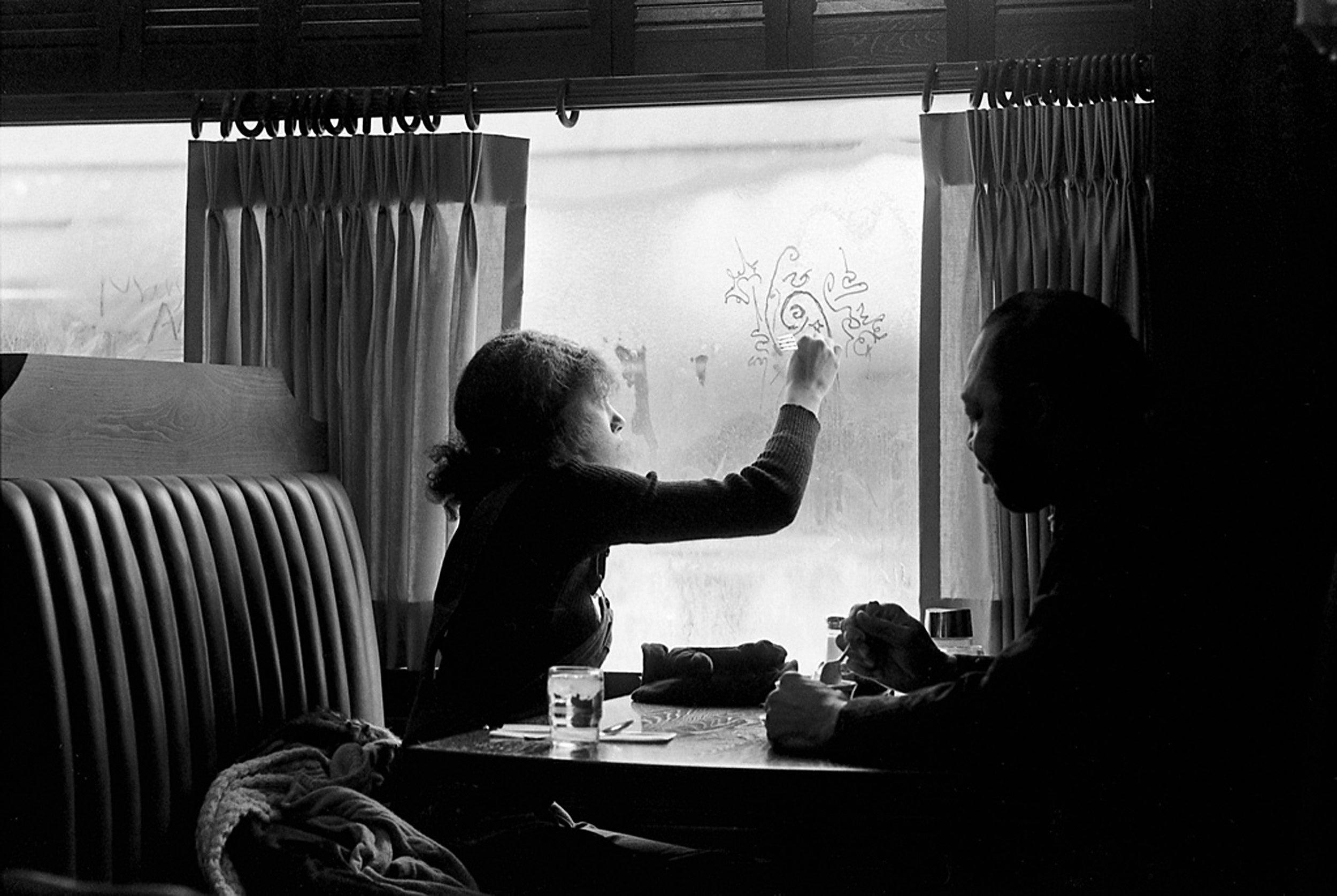 Woman in restaurant booth doodles in window fog, 1969.