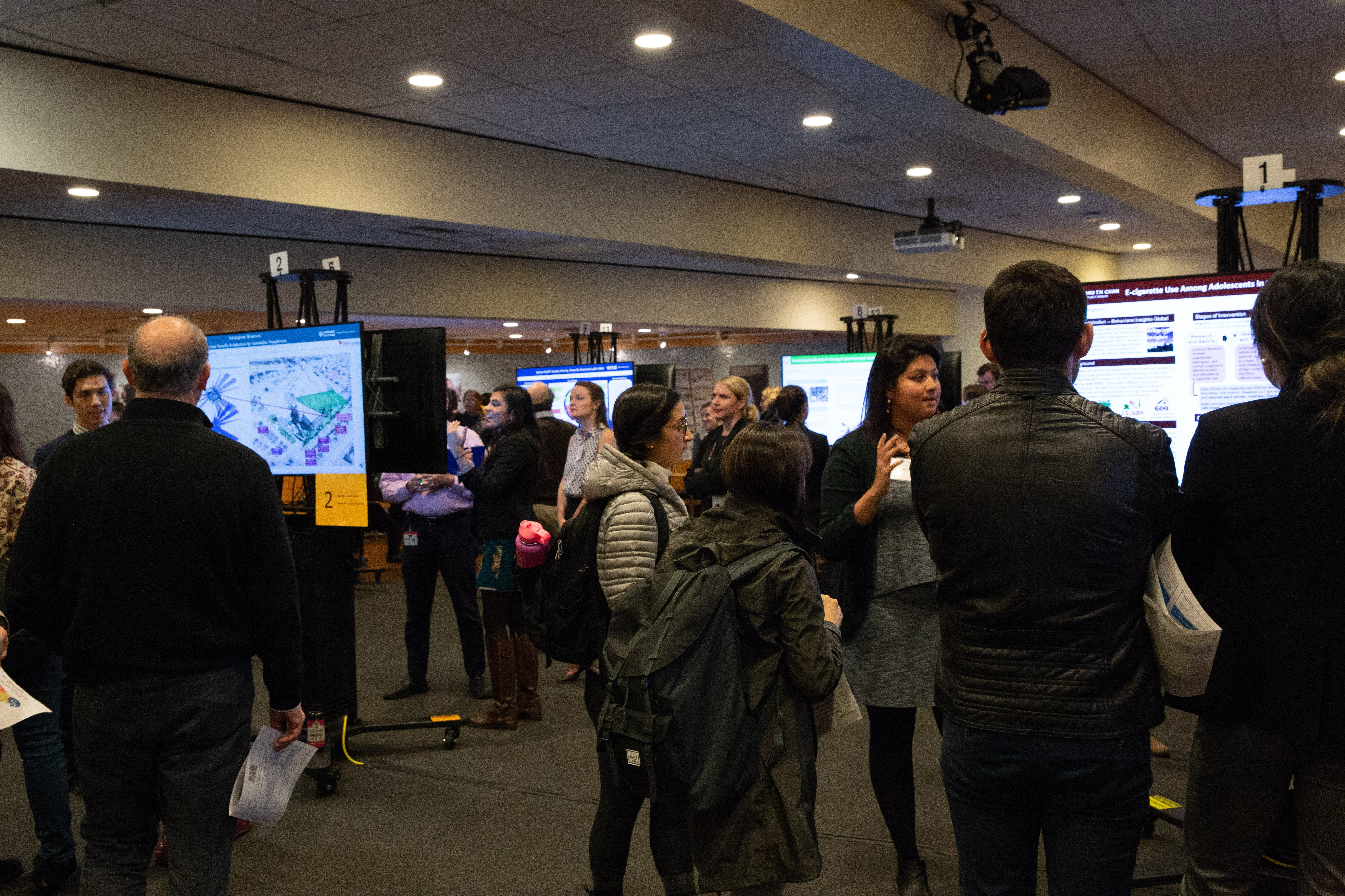 MPH students at Harvard T.H. Chan School of Public Health display and discuss their field work. Photos: Nilagia McCoy