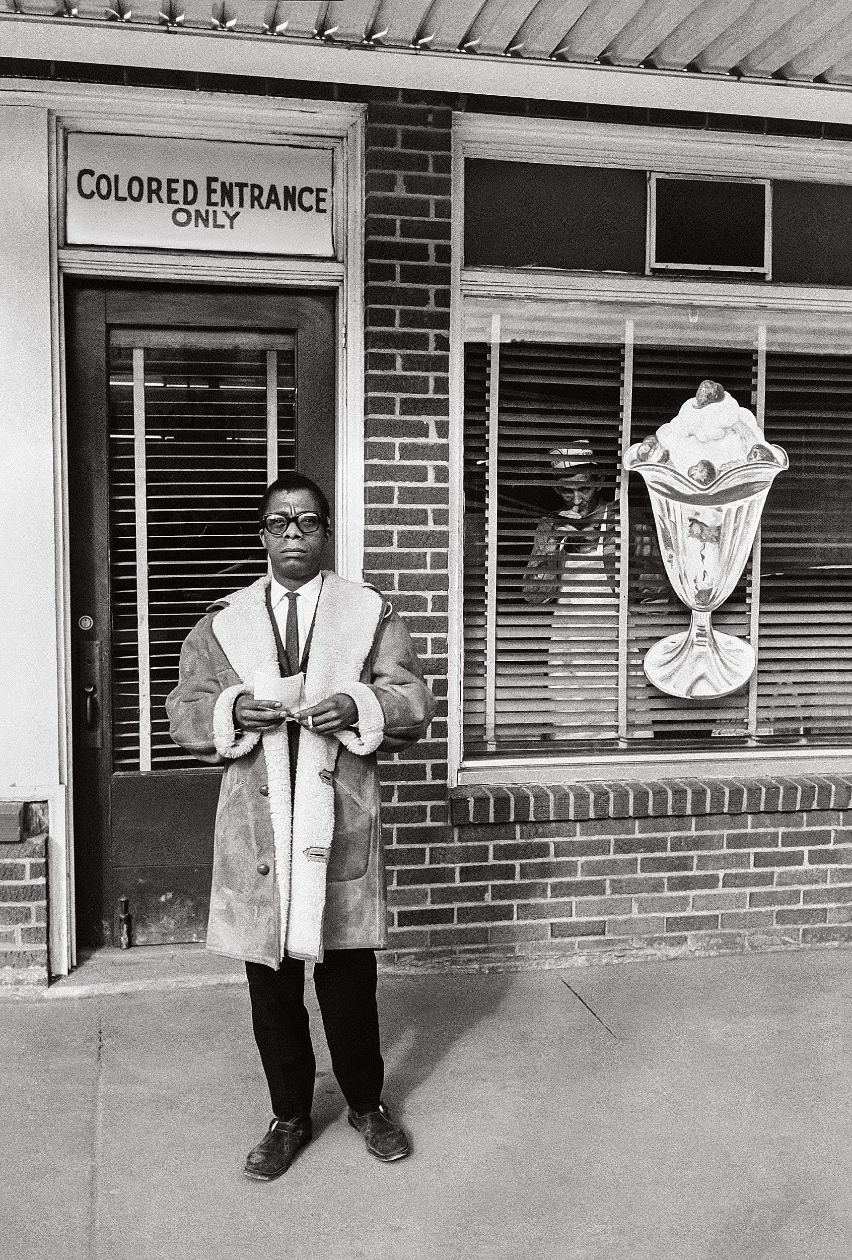 "James Baldwin stands in front of ""Colored entrance only"" sign in New Orleans, 1963."