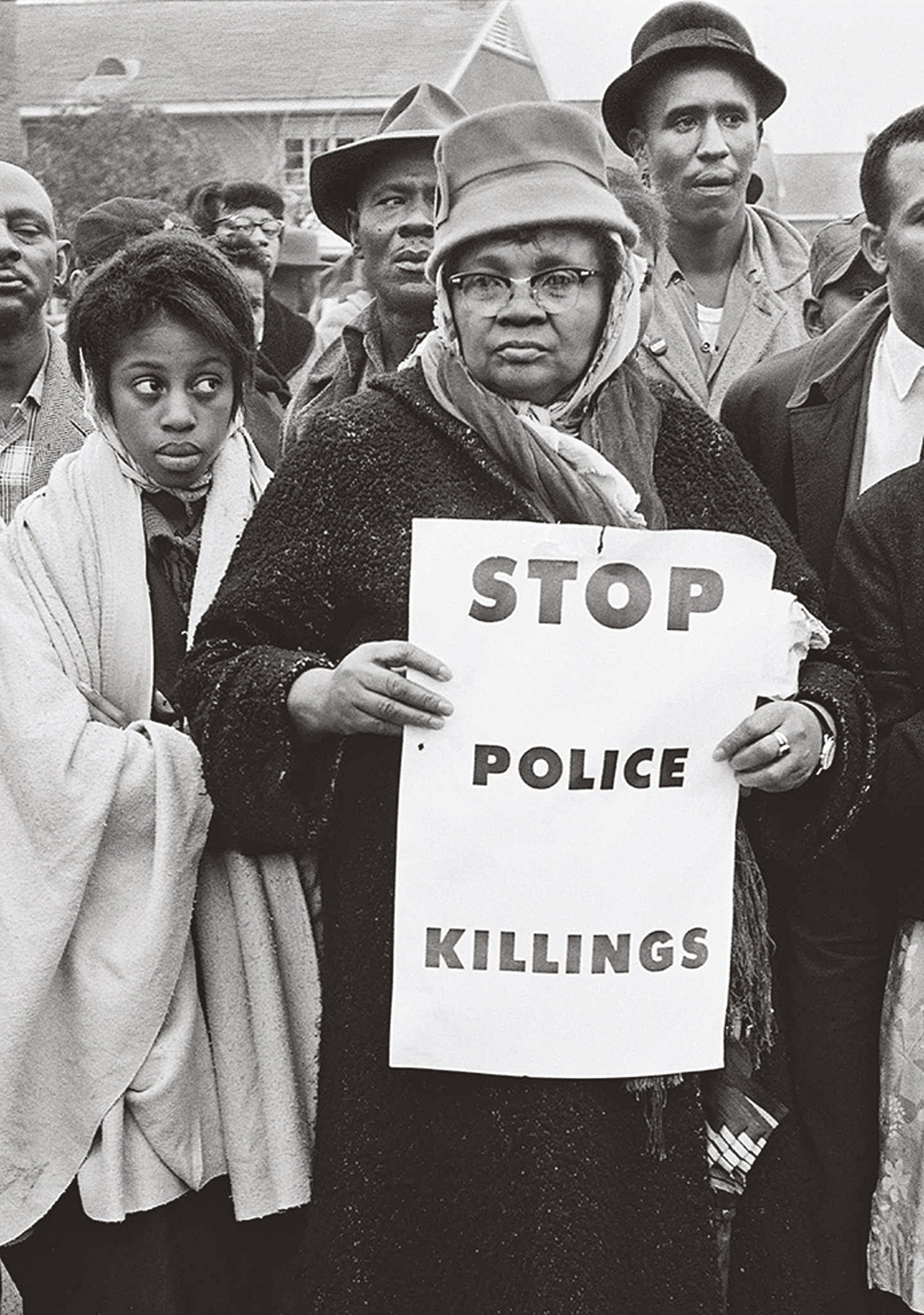 "Women holds sign that says ""Stop police killings"" in 1965."