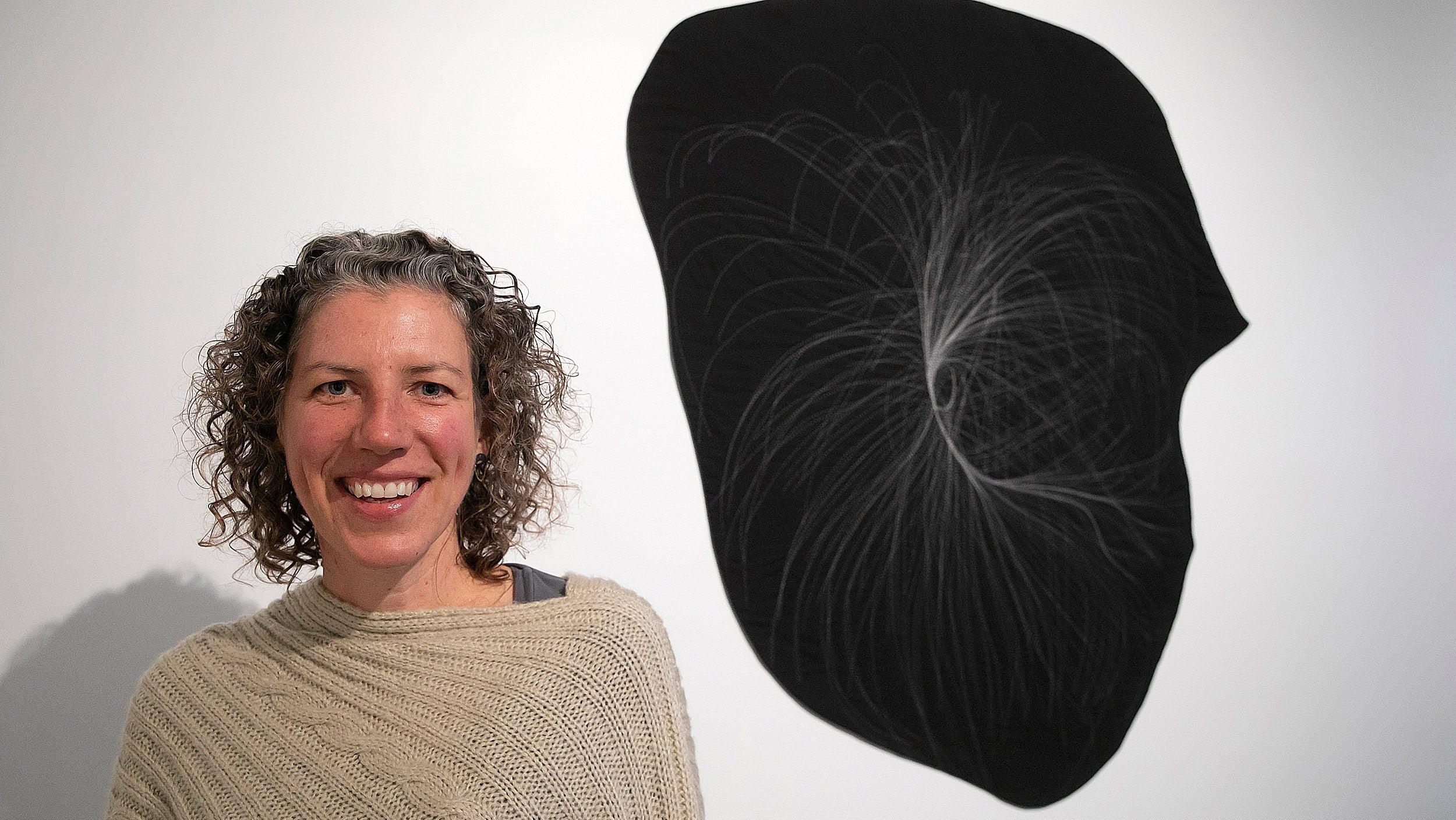 Artist Anna von Mertens with one of her quilts mapping stars.