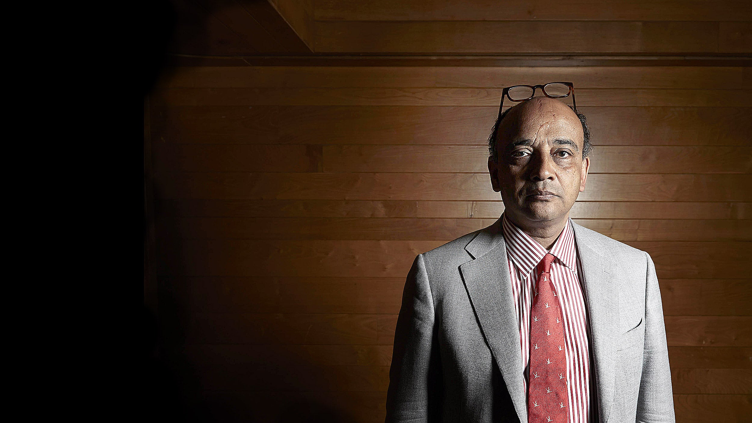Kwame Anthony Appiah in front of a wooden wall