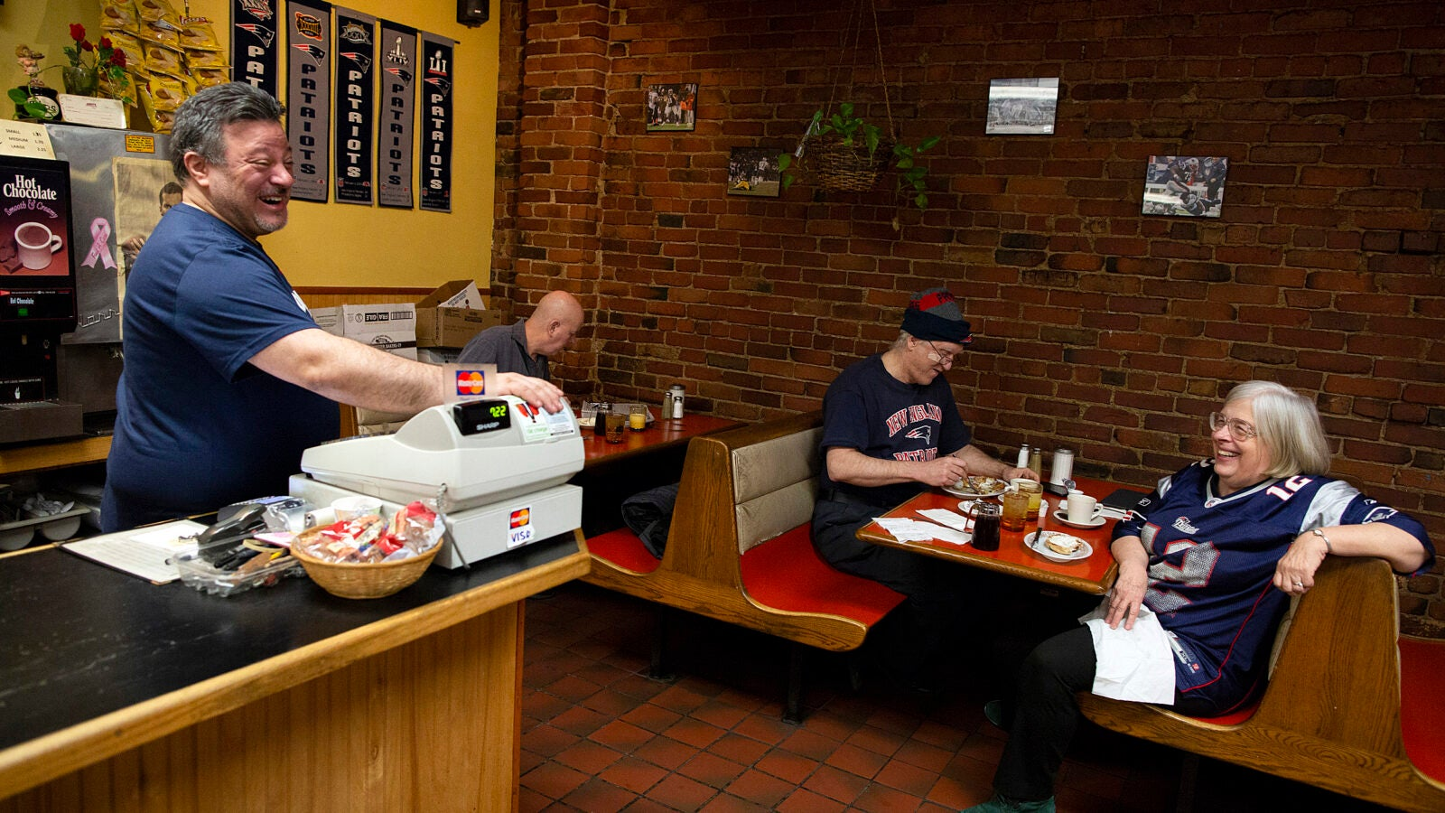 Jimmy Dres (from left) the owner of Andy's Diner in Cambridge talks football with Tom Cunningham, building manager of the Harvard University Press, and physicist Bill Skocpol and his wife Theda Skocpol, Harvard's Victor S. Thomas Professor of Government and Sociology. The restaurant is a local favorite for a group of early-rising fans who love Monday-morning quarterbacking.