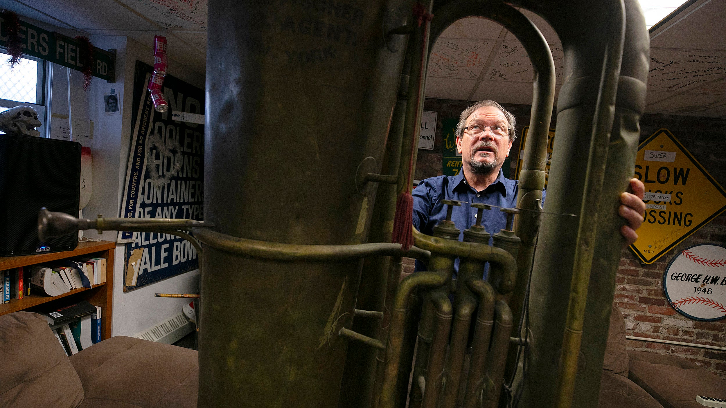 A man standing behind a giant tuba