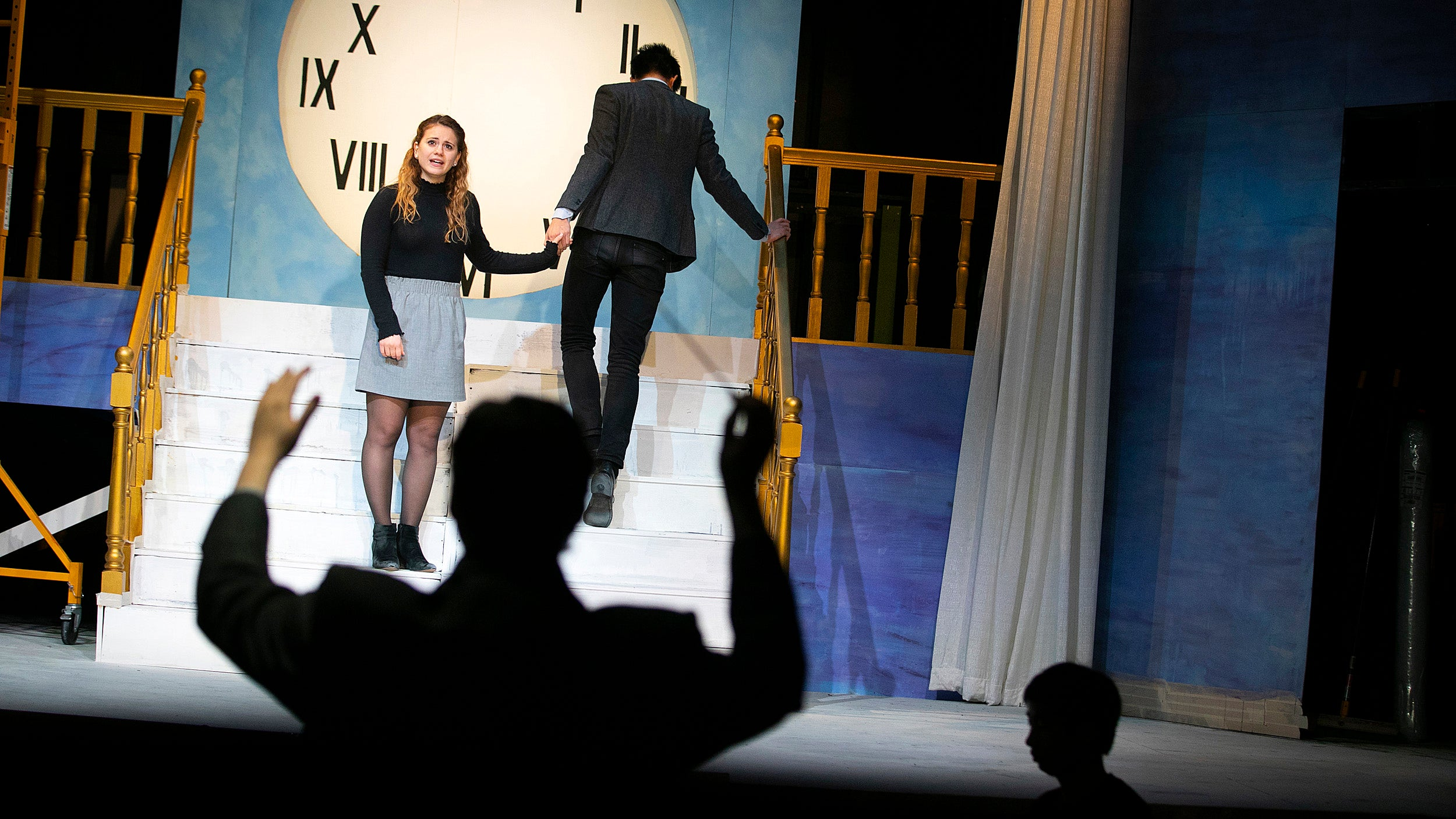 """Harvard College Opera rehearsing """"Cendrillon."""" Arianna Paz '19 (from left) and Alex Chan '22 perform on the stage as Benjamin Wenzelberg '21 conducts."""