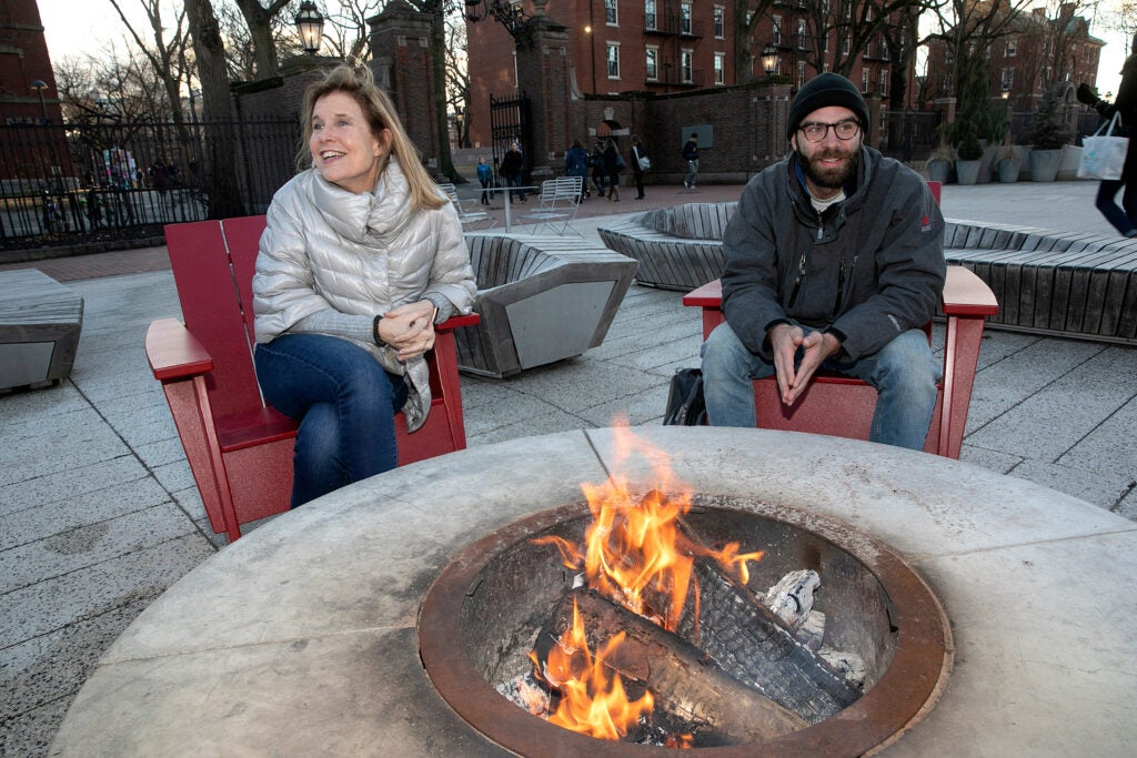 Two people sitting around a fire pit