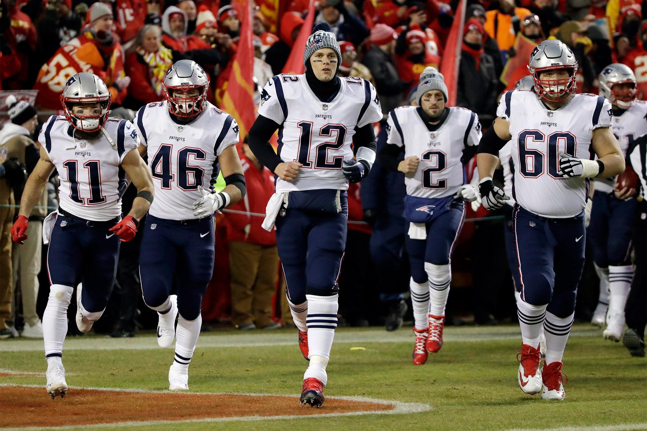 Tom Brady leads the Patriots onto the field.