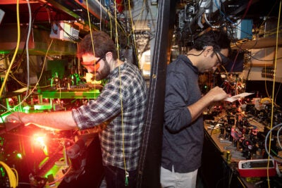 Louis Baum (left) and Debayan Mitra prepare to use lasers to cool polyatomic molecules in Physics Professor John Doyle's lab. The buffer-gas cooling method pioneered in the lab is being explored for applications as diverse as disease detection and analysis of flavor profiles.