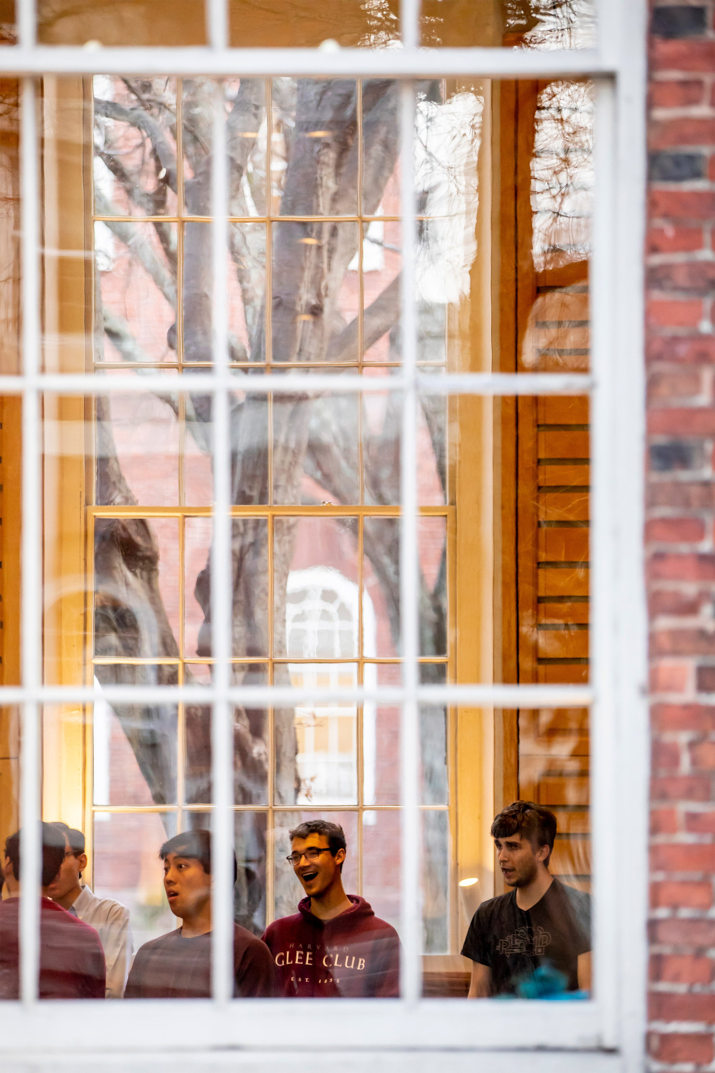 Through a window, the Harvard Glee Club rehearses.