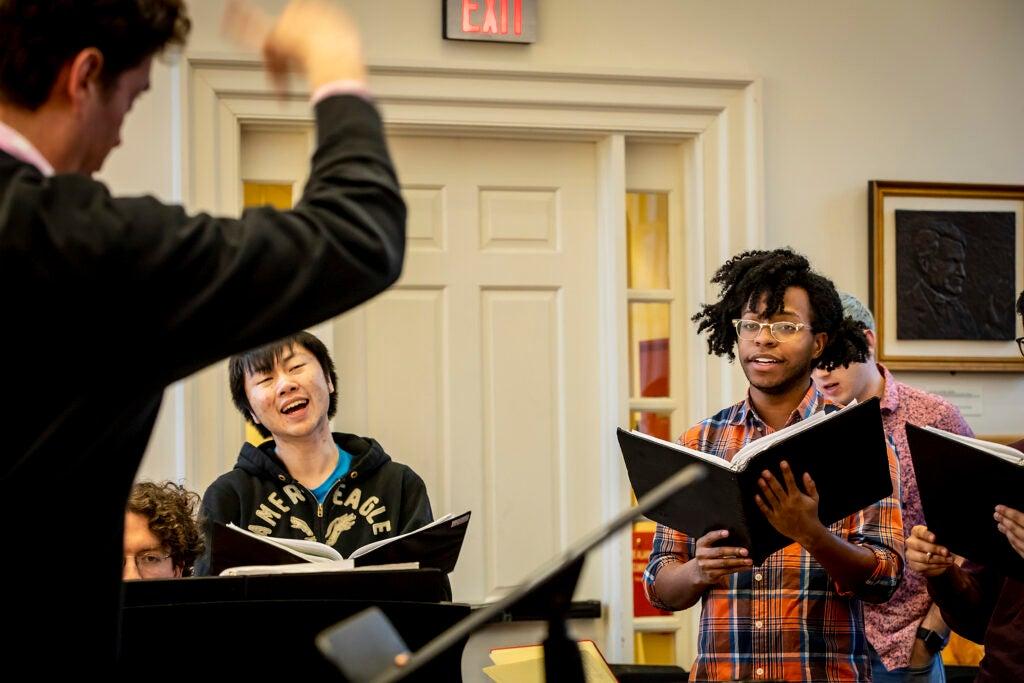 The Harvard Glee Club rehearses, led by Andrew Clark.