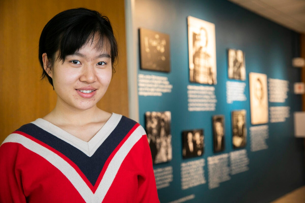 Xue (Snow) Dong in front of the photo wall in Currier House