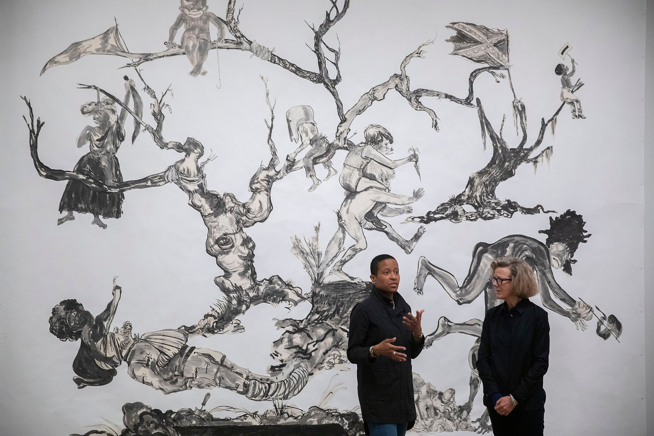 Chassidy Winestock and Mary Schneider Enriquez with Kara Walker's art U.S.A Idioms..