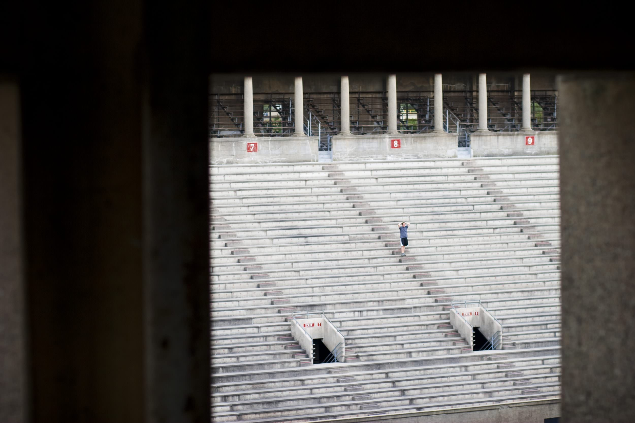 A runner stands on the steps of Harvard Stadium stairs.