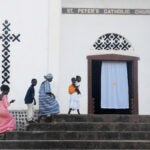 Worshippers arrive for Sunday mass at St. Peter's Church in Kamakwie, Sierra Leone.
