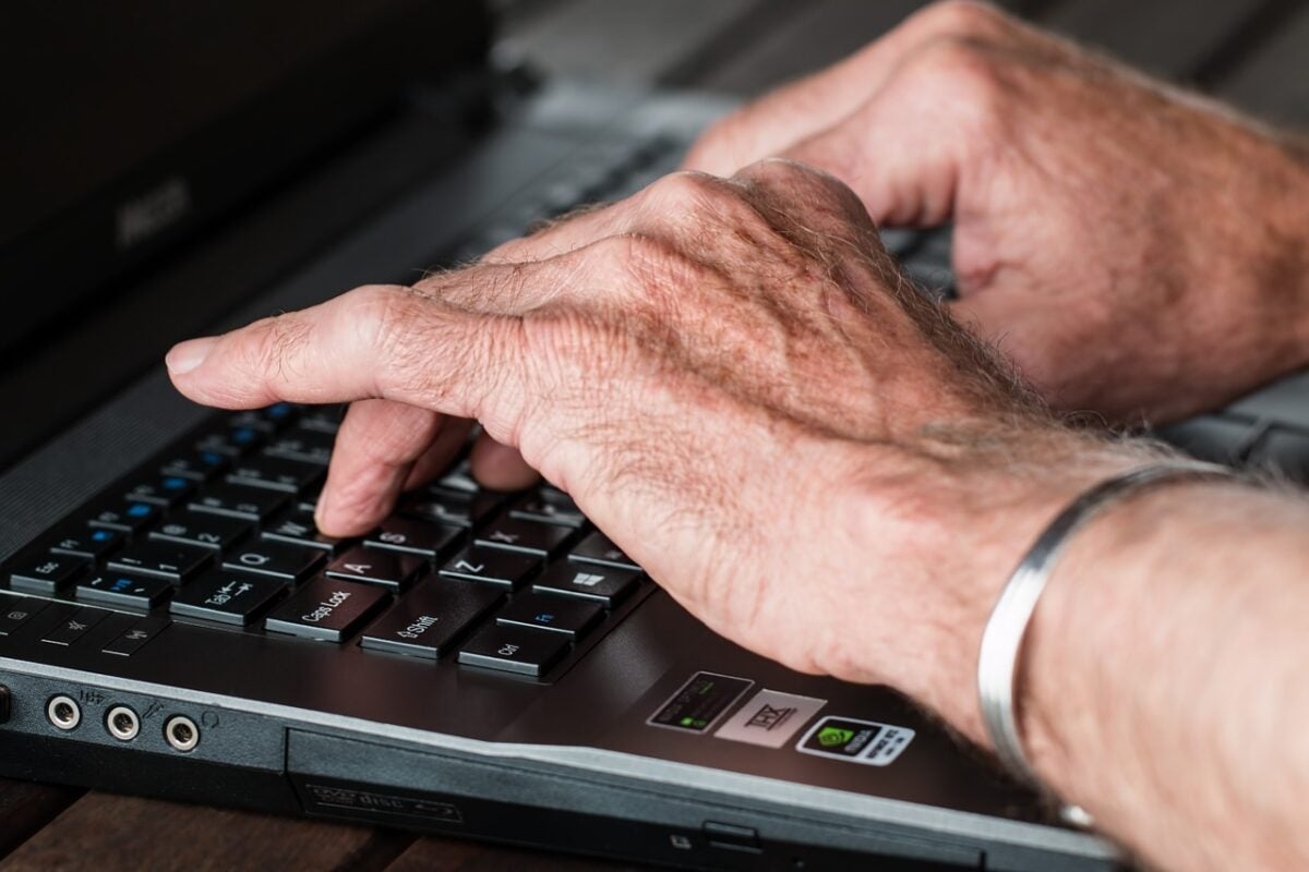 Arthritic hands typing on a keyboard.