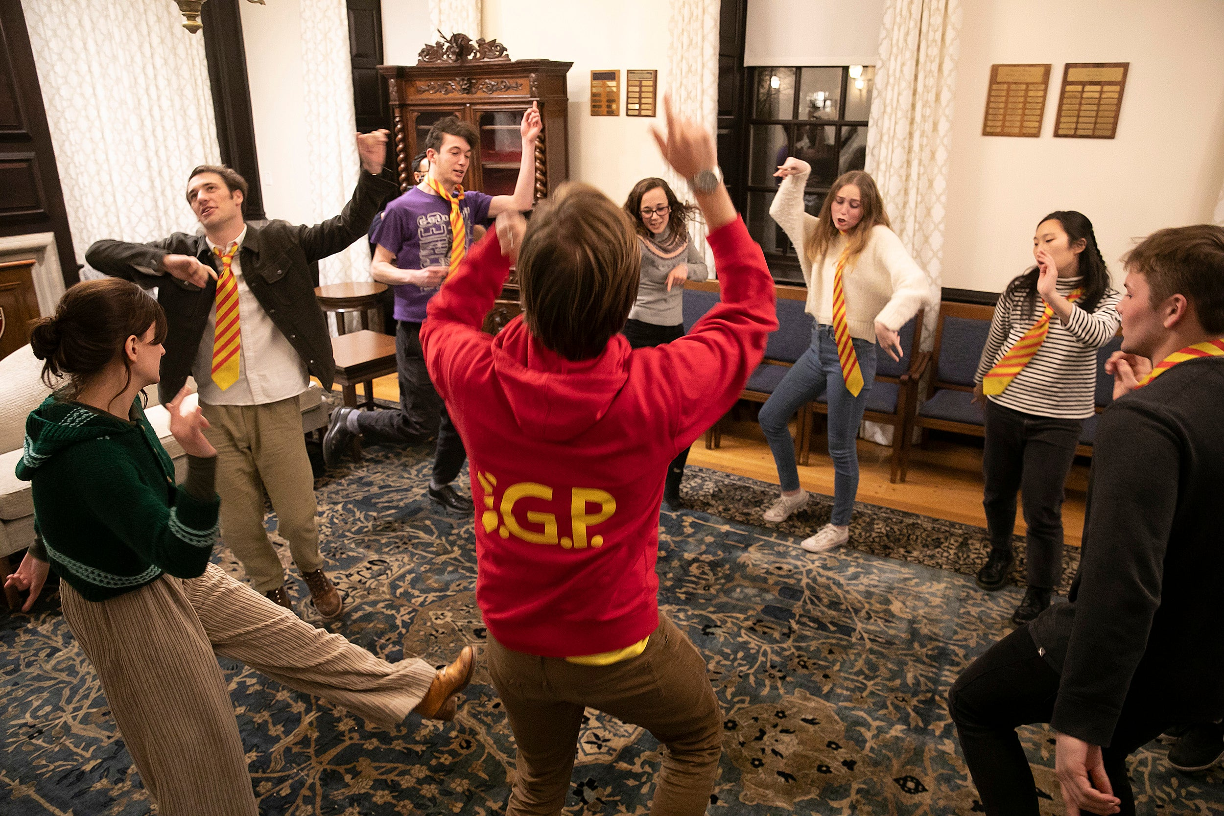 Students in a circle strike poses to practice their improv techniques.