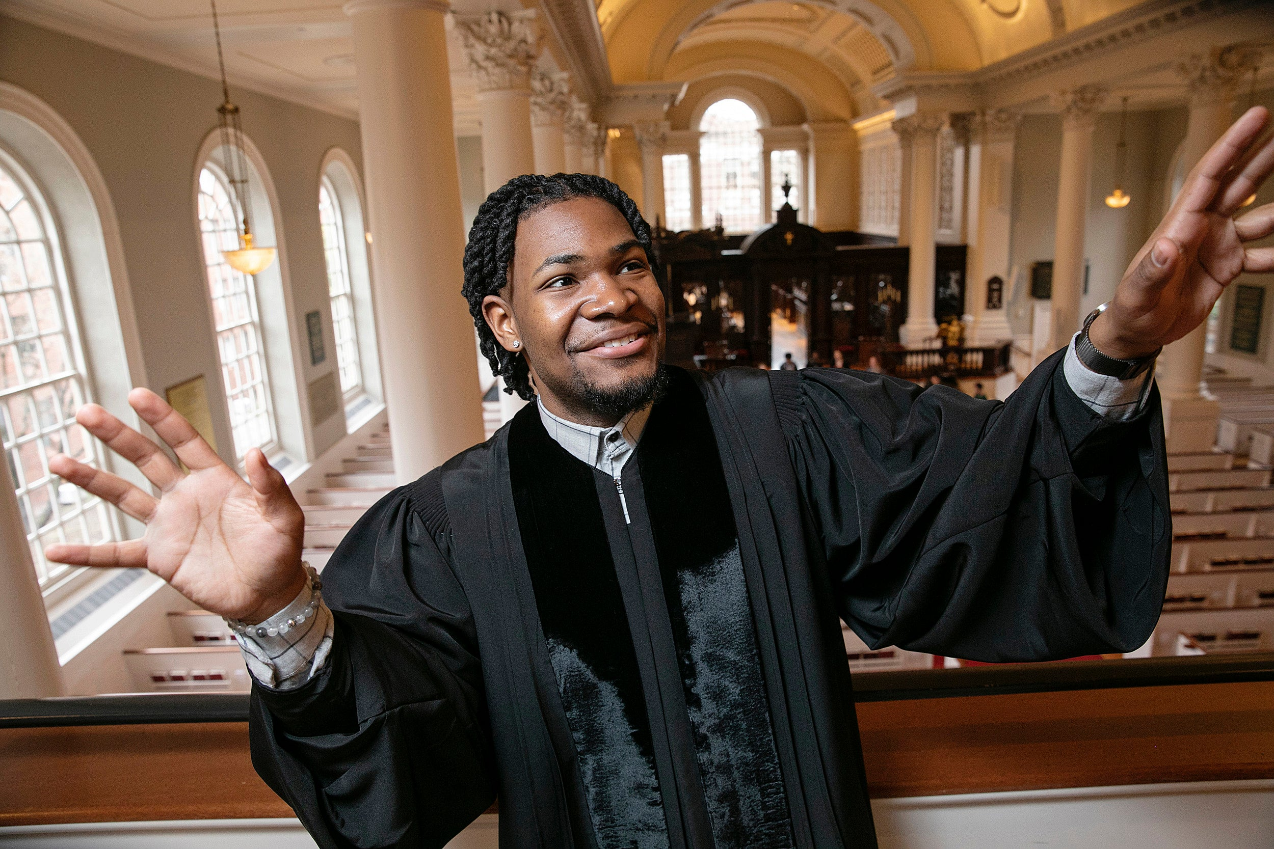 Aric Flemming in a priest's gown standing in church