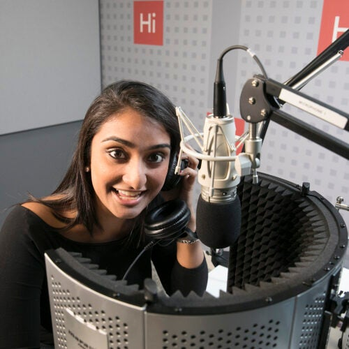 Shah talking into a microphone