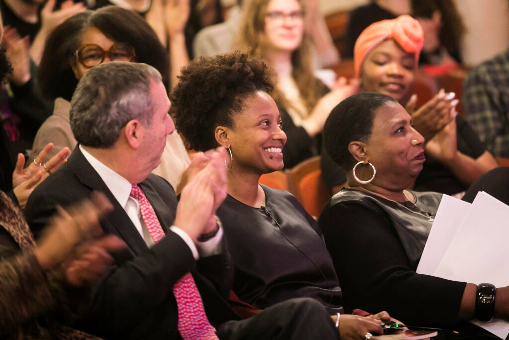 U.S. poet laureate Tracy K. Smith '94, center, is applauded by Harvard President Larry Bacow, left, and journalist Callie Crossley, right