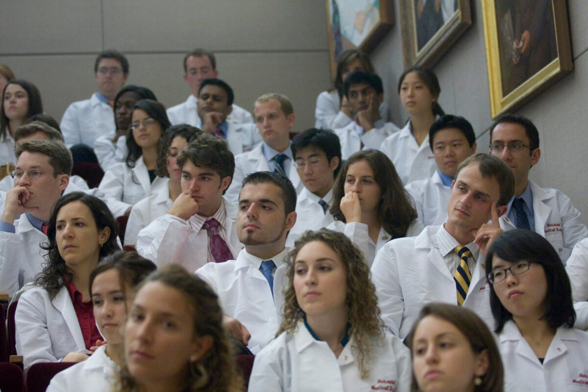A group of doctors sit in an auditorium