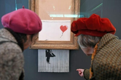 Two women wearing red berets inspect the shredded Banksy painting at the Museum Frieder Burda in Baden-Baden.