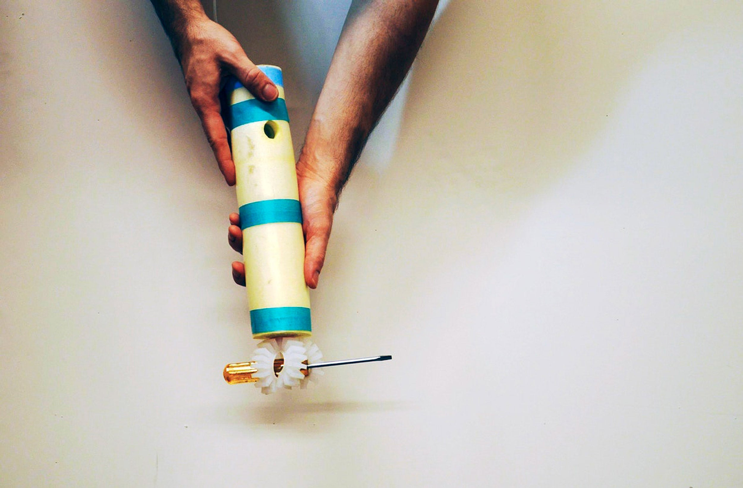 The toggle gripper holds a screwdriver.