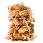 A tower of junk food including fried chicken, hamburgers, hot dogs, french fries, and cupcakes.