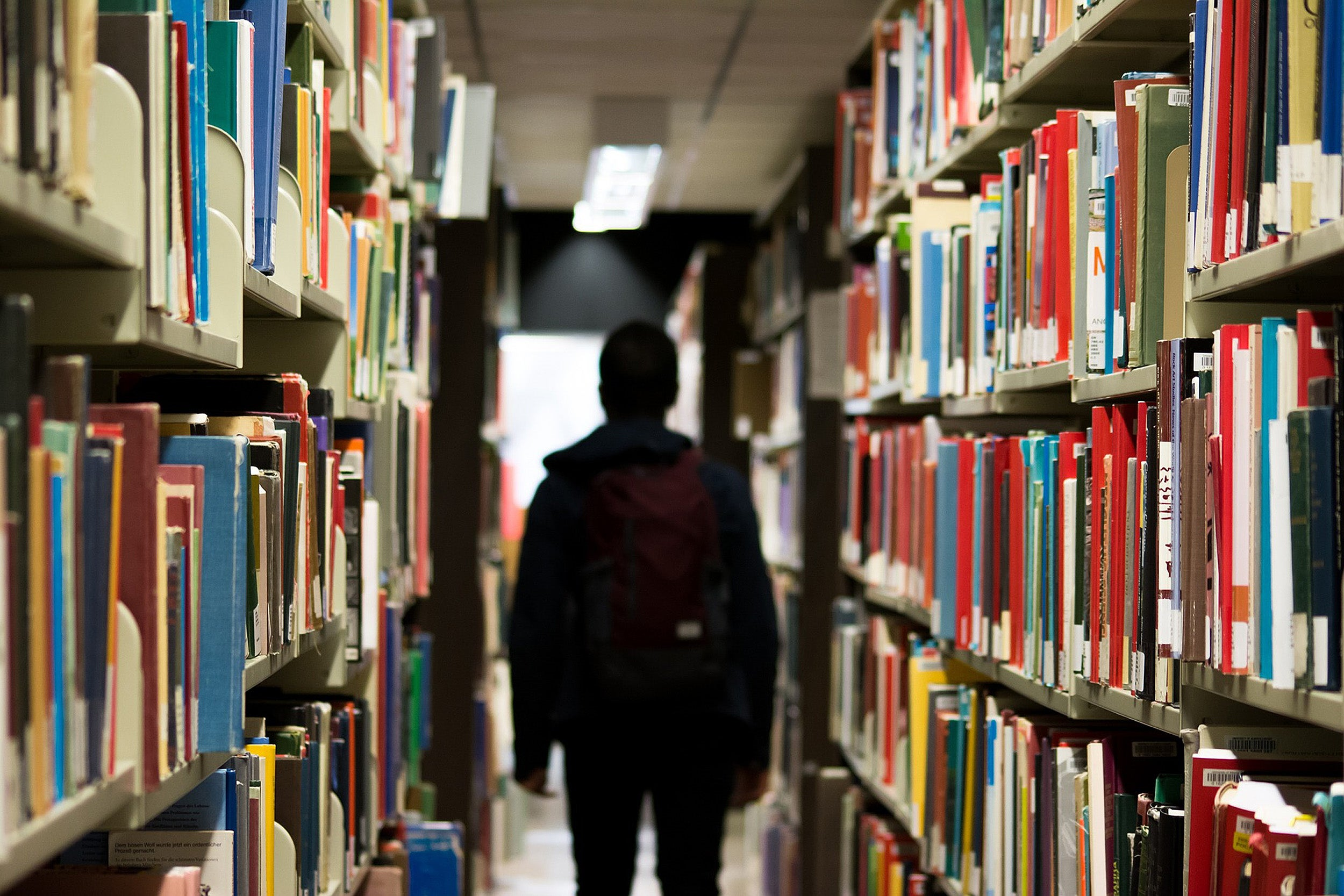 A person in silhouette between library book shelves